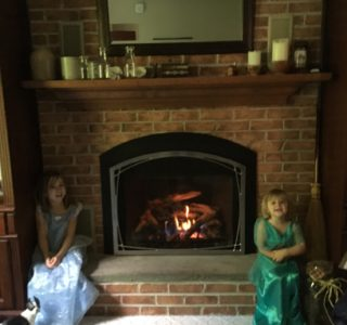 children sitting by fireplace