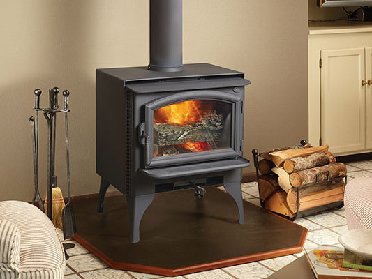 black wood stove with logs next to fire