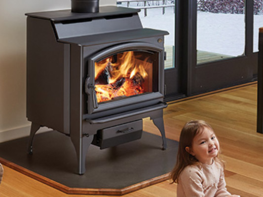 little girl sitting infront of wood stove