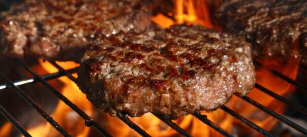 Burgers being grilled over wood chips and charcoal